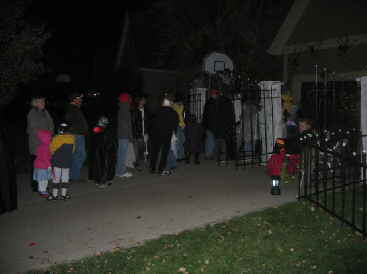 Trick or treaters visiting spookystreet.com walk through haunted house